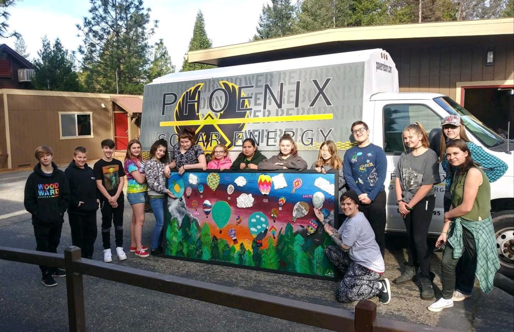 Students display their mural that will eventually hang at the school. (Ashley Bailey/Here & Now)