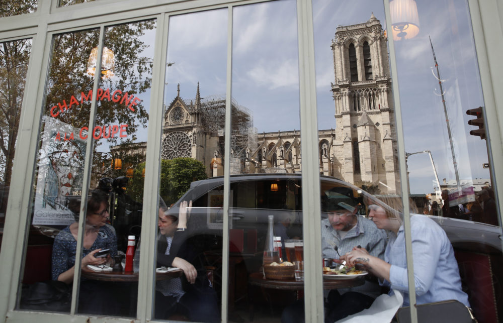 People eat at a cafe with the Notre Dame Cathedral reflected in the window in Paris, Thursday, April 18, 2019. (Christophe Ena/AP)