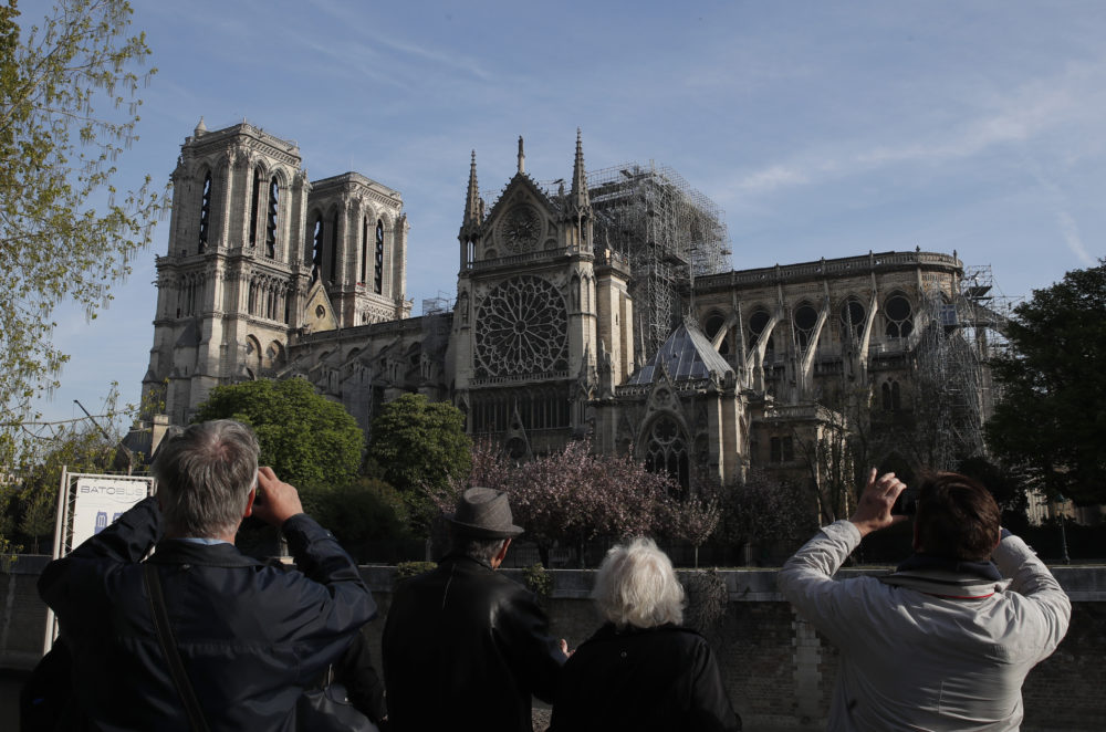 People take photos of the Notre Dame Cathedral from the Left Bank in Paris, Thursday, April 18, 2019. (Christophe Ena/AP)
