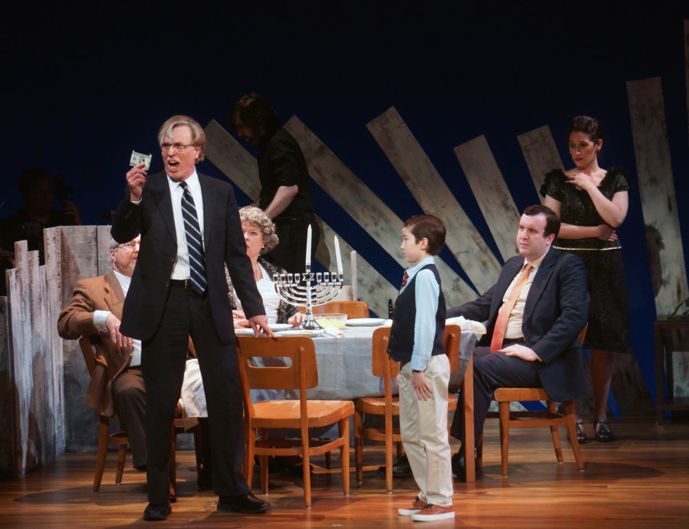 Mr. Stopnick (Phil Thompson) rails against capitalism to Noah (Ben Choi-Harris) while the rest of the family looks on bemusedly. (Courtesy Sharman Altshuler)