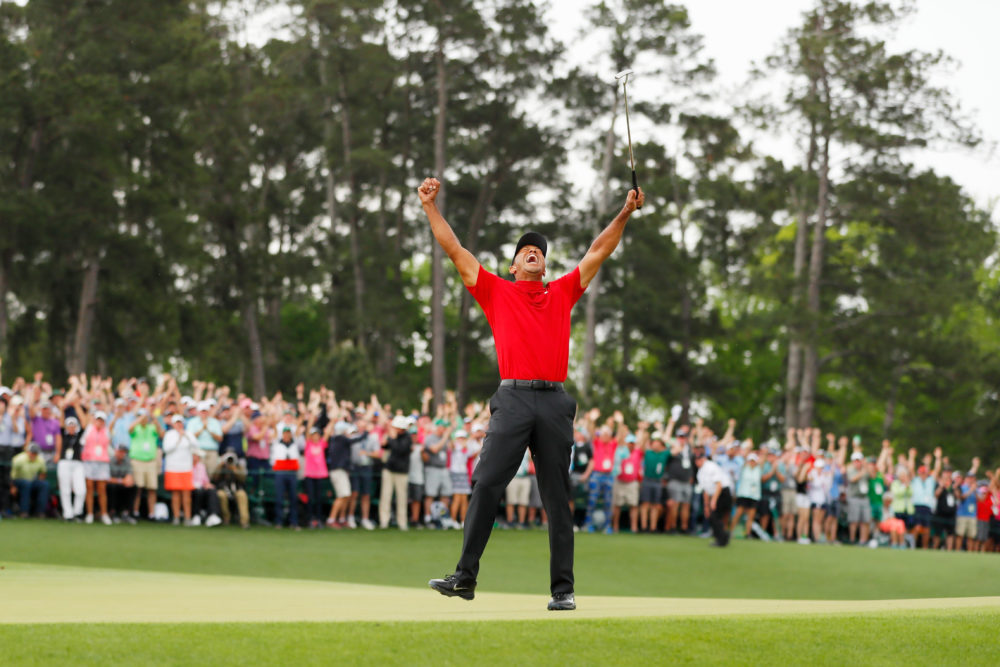 Tiger Woods celebrates after making his putt on the 18th green to win his fifth Masters title. (Kevin C. Cox/Getty Images)