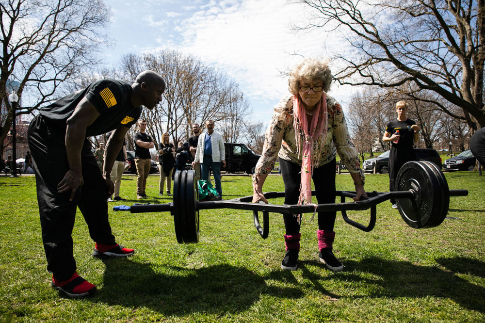 """Jadwiga Serafin, of Poland, is coached by Sgt. First Class Anthony Darrison while trying the dead lift at Boston Common. Serafin, who is 62, exclaimed, """"This is nothing!"""" and asked for more weight. (Erin Clark for WBUR)"""