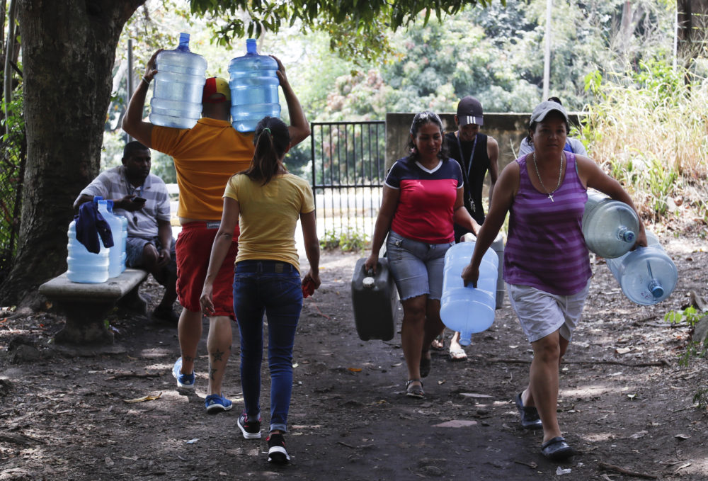 People carry containers to fill with water in Avila National Park during rolling blackouts that have cut many off from running water in Caracas, Venezuela, on March 13, 2019. (Eduardo Verdugo/AP)