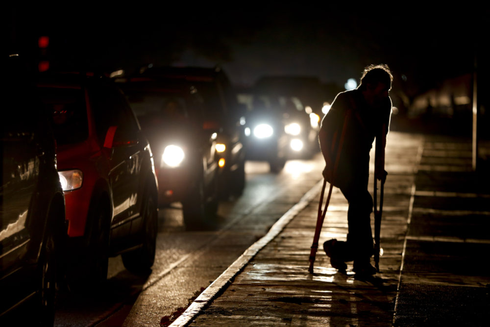 A man on crutches is illuminated by headlights of oncoming traffic, in Caracas, Venezuela during a blackout on March 29. Venezuelans are struggling to understand the Sunday, March 31, 2019 announcement that the nation's electricity is being rationed to combat daily blackouts. (Natacha Pisarenko/AP)
