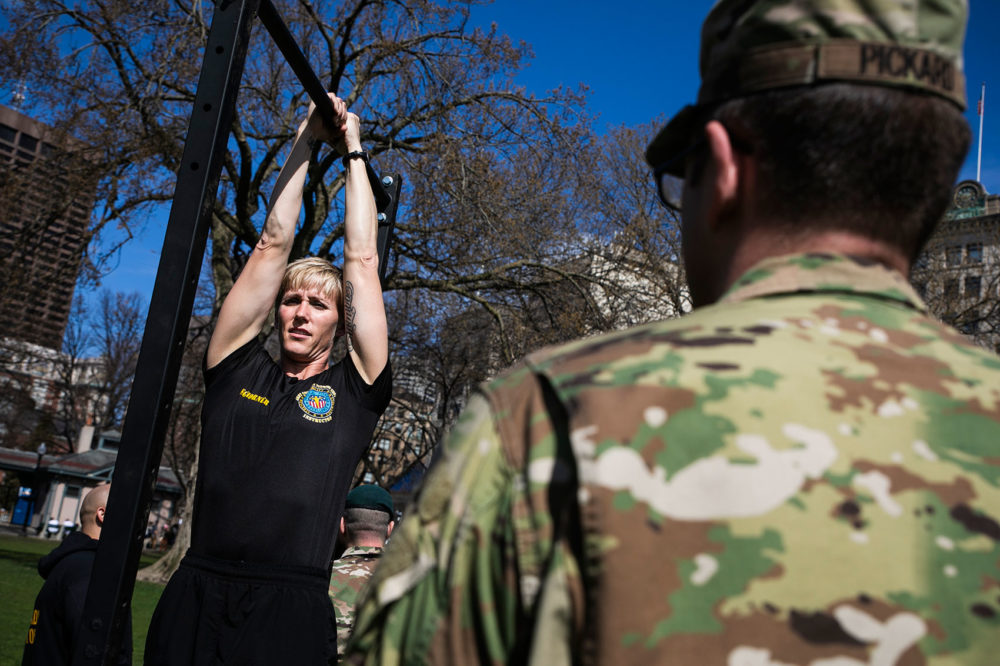 Master Sgt. Shelley Horner, fitness trainer for the Texas Army National Guard, demonstrates a leg tuck. (Erin Clark for WBUR)