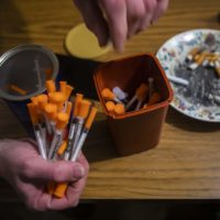 A drug user in Lewiston, Maine, disposes used needles into a one quart-sized sharps container to be exchanged for brand new supply of needles. (Jesse Costa/WBUR)