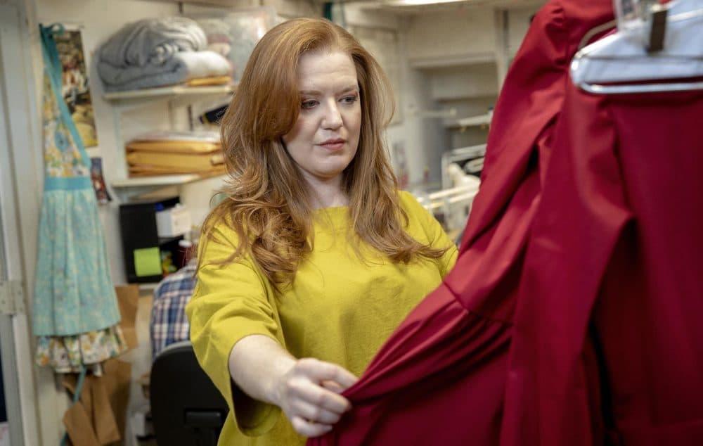 Jennifer Johnson Cano looks through Handmaids' costumes on a visit to Costume Works. (Robin Lubbock/WBUR)