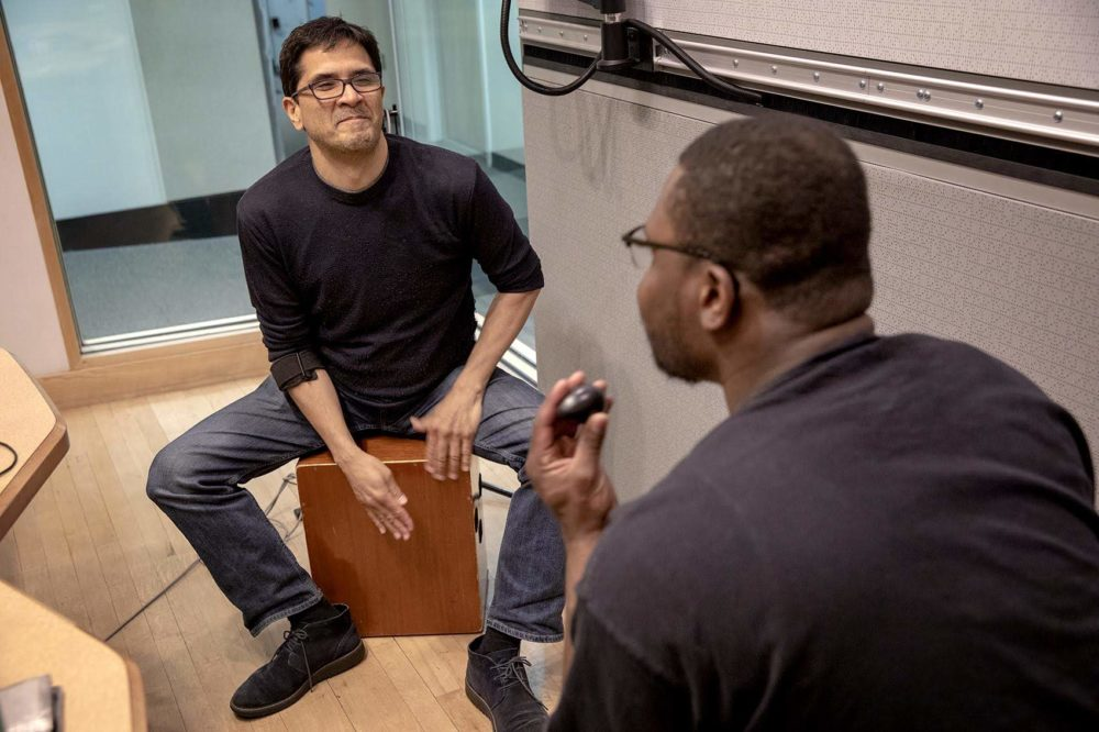 Jorge Perez-Albela plays a cajon, while Jonathan Mande plays cajon and shaker. (Robin Lubbock/WBUR)