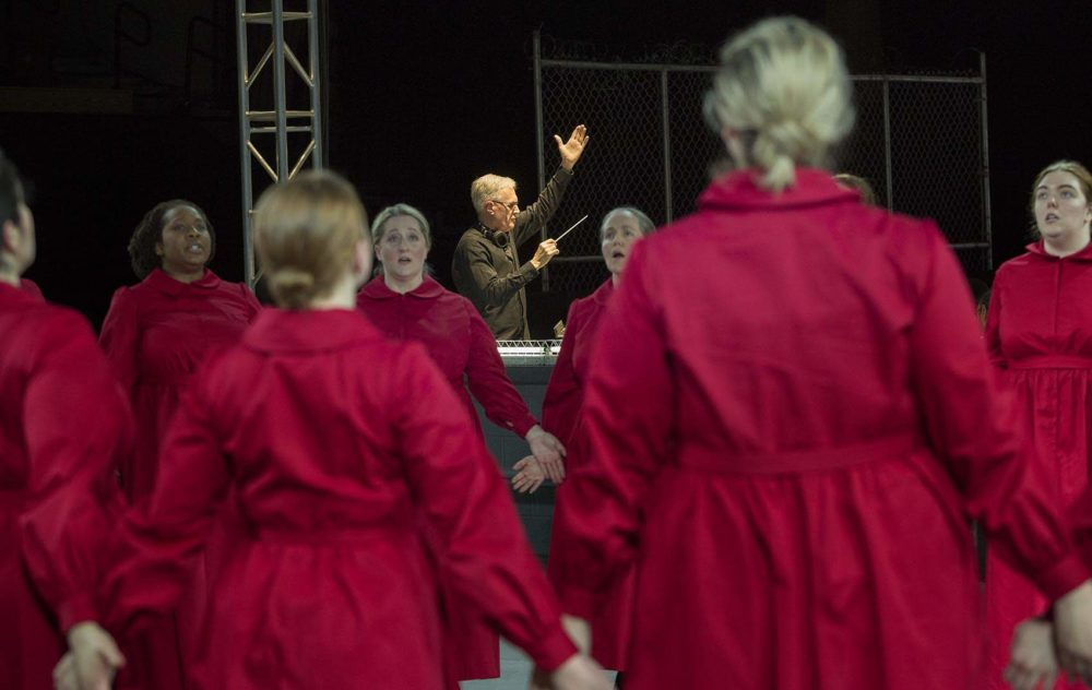 """David Angus conducts as Handmaids circle on the stage at a rehearsal of """"The Handmaid's Tale."""" (Robin Lubbock/WBUR)"""