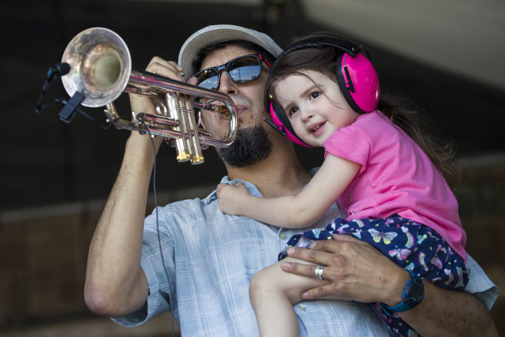 Eric Lucero holds his daughter Ava Lucero, 2, as he plays the trumpet onstage with Sunpie & the Louisiana Sunspots at the Fais Do Do stage during the New Orleans Jazz & Heritage Festival, Sunday, April 28, 2019, in New Orleans. (Alex Brandon/AP)