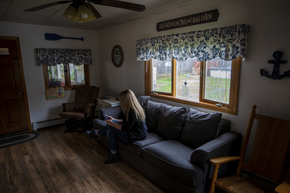 A woman whose last name is Smith, seen here in a family member's Massachusetts home, says she was sexually assaulted by a guard for Prisoner Transportation Services while being returned to the state for a probation violation. (Jesse Costa/WBUR)