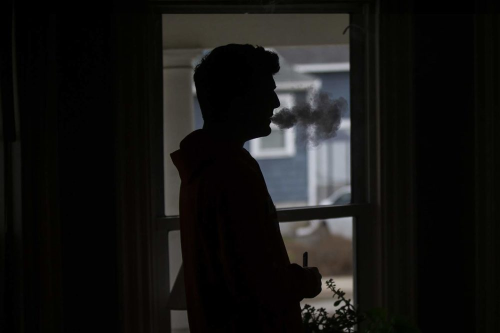A teen uses a JUUL vaping device. (Jesse Costa/WBUR)