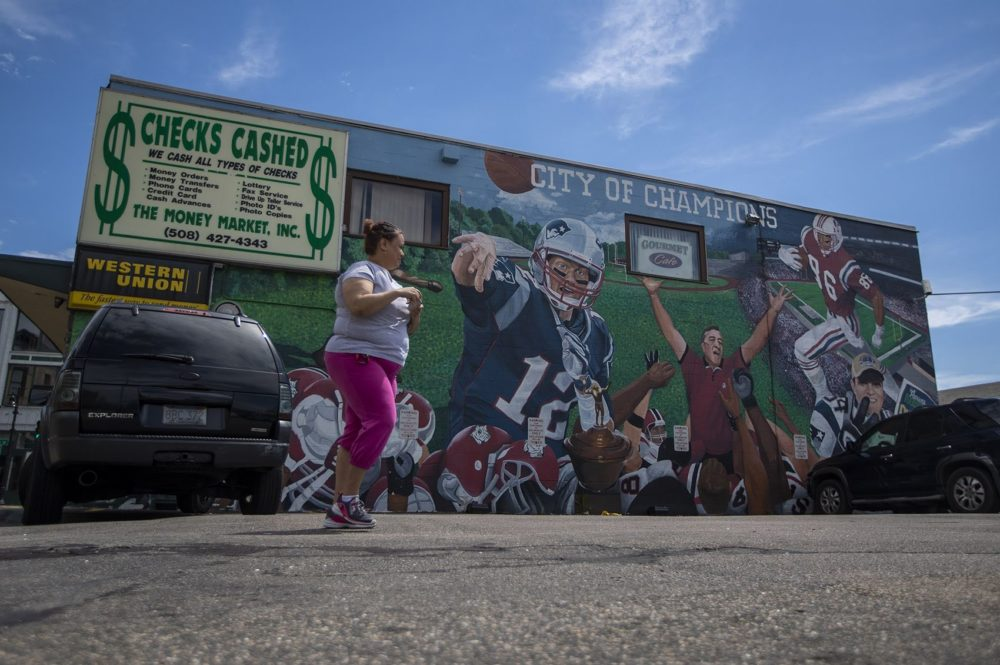 "A woman walks past a mural depicting Boston as it's commonly referred to as the ""City of Champions."" (Jesse Costa/WBUR)"
