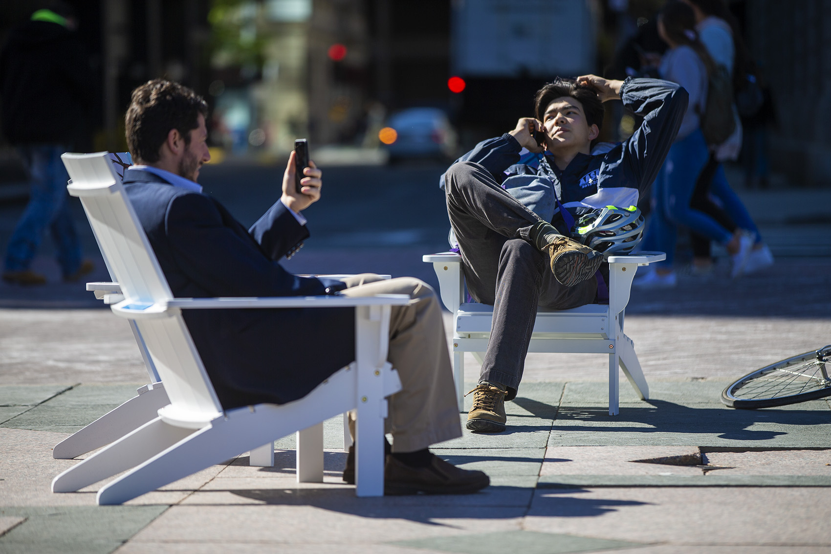 Marc Chan, right, calls his father while sitting on one of the Artists For Humanity-painted Adirondack chairs in Copley Square. (Jesse Costa/WBUR)