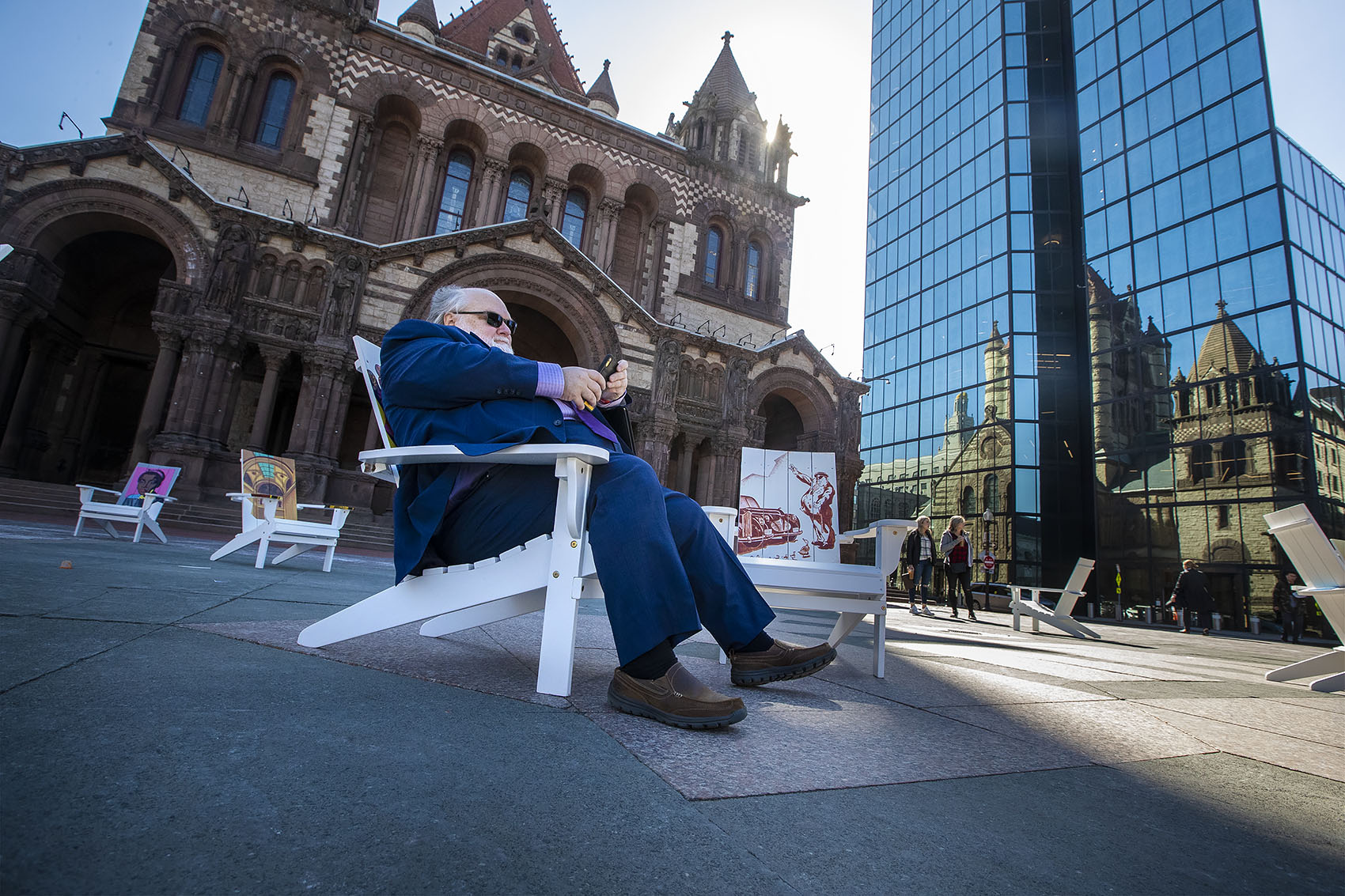 Jerome Wolter stops and sits on one of the Adirondack chairs on his way to a job interview. (Jesse Costa/WBUR)
