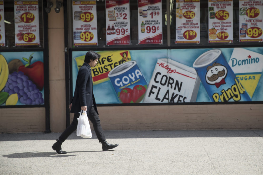 A man leaves a supermarket in the East Village neighborhood of Manhattan carrying his groceries in a plastic bag on March 27. (Mary Altaffer/AP)
