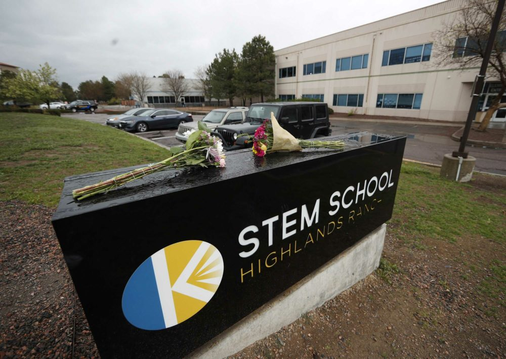 Bouquets of flowers sit on the sign outside the STEM School Highlands Ranch late Wednesday, May 8, 2019, in Highlands Ranch, Colo. A shooting took place Tuesday at the charter school south of Denver. (David Zalubowski/AP)