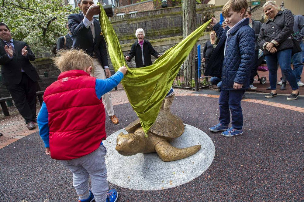 """Sculptor Nancy Schön cheers from behind as Miguel Rosales, left, and three young helpers unveil the bronze recreation of """"Myrtle The Turtle,"""" the famed green sea turtle of the New England Aquarium, at the Myrtle Street Playground on Beacon Hill. (Jesse Costa/WBUR)"""