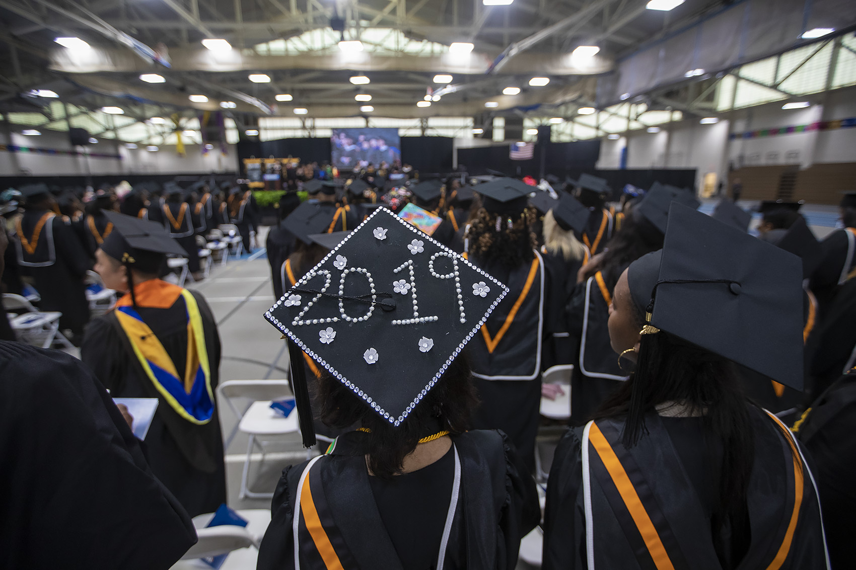 Graduates of Roxbury Community College stand at their seats during the commencement at Reggie Lewis Arena. (Jesse Costa/WBUR)