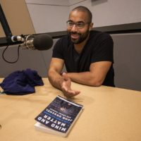 "John Urschel with his new book ""Mind And Matter."" (Jesse Costa/WBUR)"