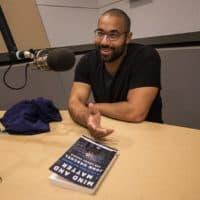 "John Urschel with his new book ""Mind And Matter."" (Jesse Costa/WBUR)"