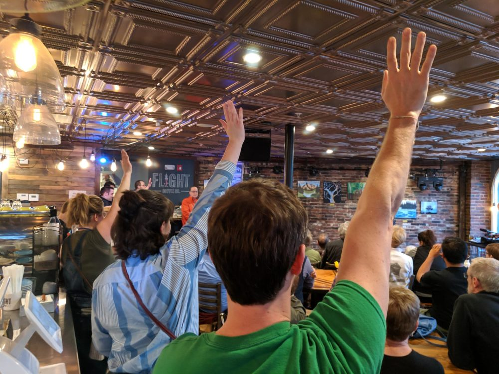 Bird-doggers raise their hands, eager to ask questions in Dover, N.H. (Jason Moon/NHPR)