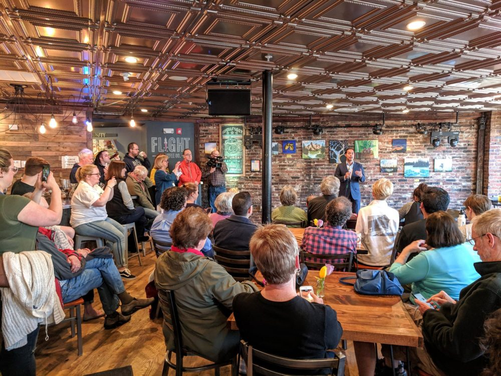 Former Housing and Urban Development Secretary Julián Castro speaks at Flight Coffee in Dover, as bird-doggers and other voters listen and wait to ask questions. (Jason Moon/NHPR)