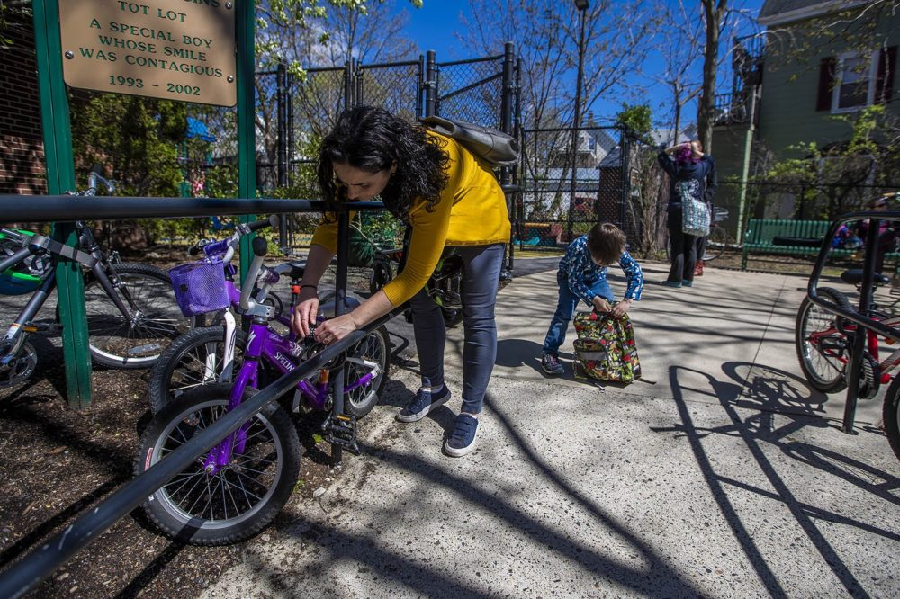 Elizabeth Pinsky unlocks her son Ben's bicycle before heading home for the day. (Jesse Costa/WBUR)