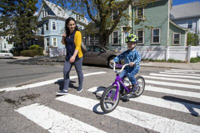 Elizabeth Pinsky walks alongside her son, Ben, while he rides his bicycle home in Somerville. (Jesse Costa/WBUR)