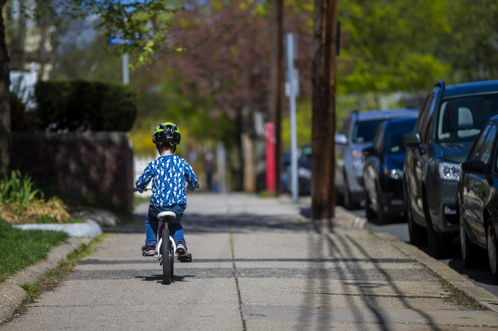 Ben rides his bike ahead of his mom on the sidewalk along College Avenue in Somerville. (Jesse Costa/WBUR)