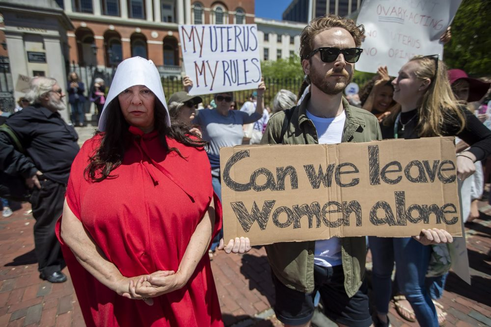 "Laura Innis, left, made the trip to Boston from Falmouth dressed as a handmaiden from ""The Handmaid's Tale"" to attend the rally. (Jesse Costa/WBUR)"