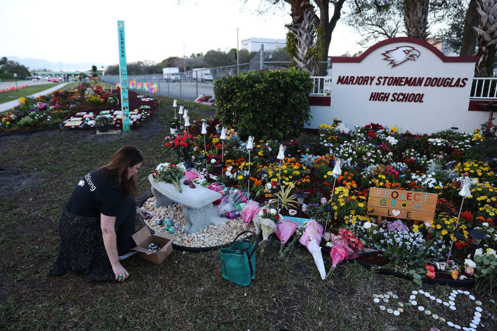 Suzanne Devine Clark visits a memorial setup at Marjory Stoneman Douglas High School for those killed during the mass shooting in Parkland, Fla. (Joe Raedle/Getty Images)