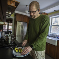 Dan slices an avocado in his kitchen. He's been on the ketogenic diet for  three years now, and says it's improved his mental health and overall well-being. (Jesse Costa/WBUR)