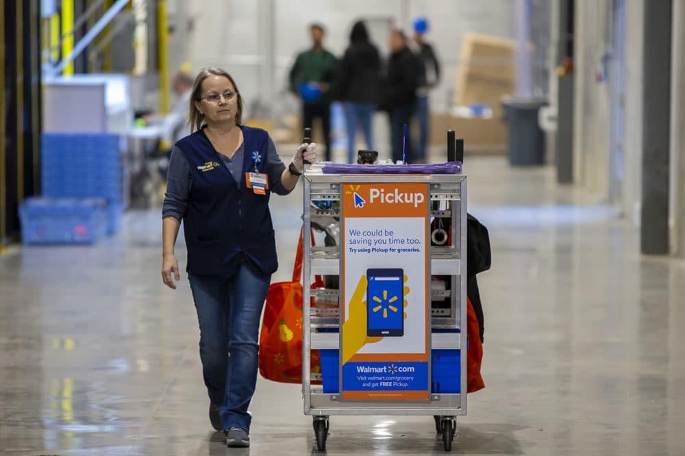 A Walmart associate rolls a cart full down the hallway of the warehouse in Salem, New Hampshire. (Jesse Costa/WBUR)