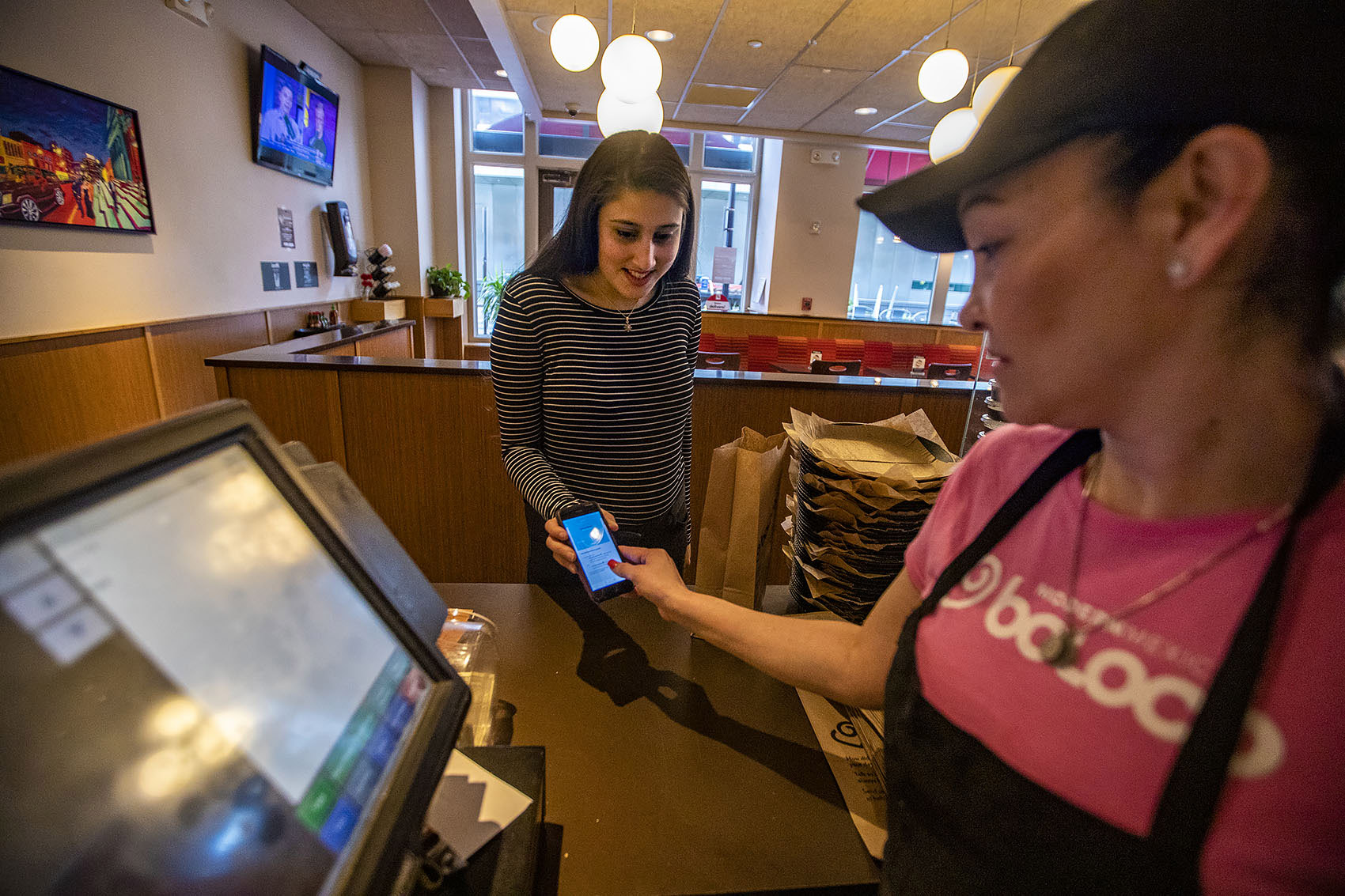 """Swathi Joshi purchases a breakfast burrito with the """"Food For All"""" app at Boloco at Atlantic Wharf. (Jesse Costa/WBUR)"""