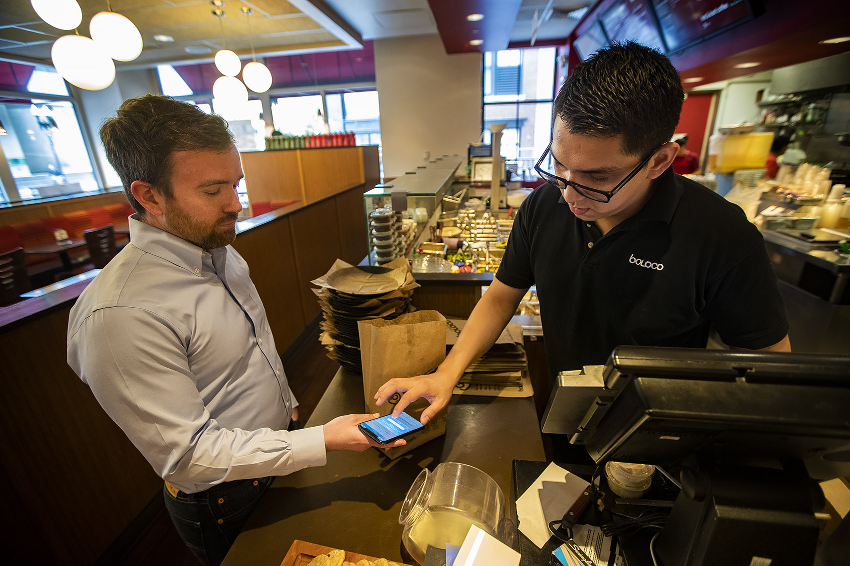 """Boloco manager Erick Guitierrez taps Tom Leonard's phone as he purchases a breakfast burrito with the """"Food For All"""" app. (Jesse Costa/WBUR)"""