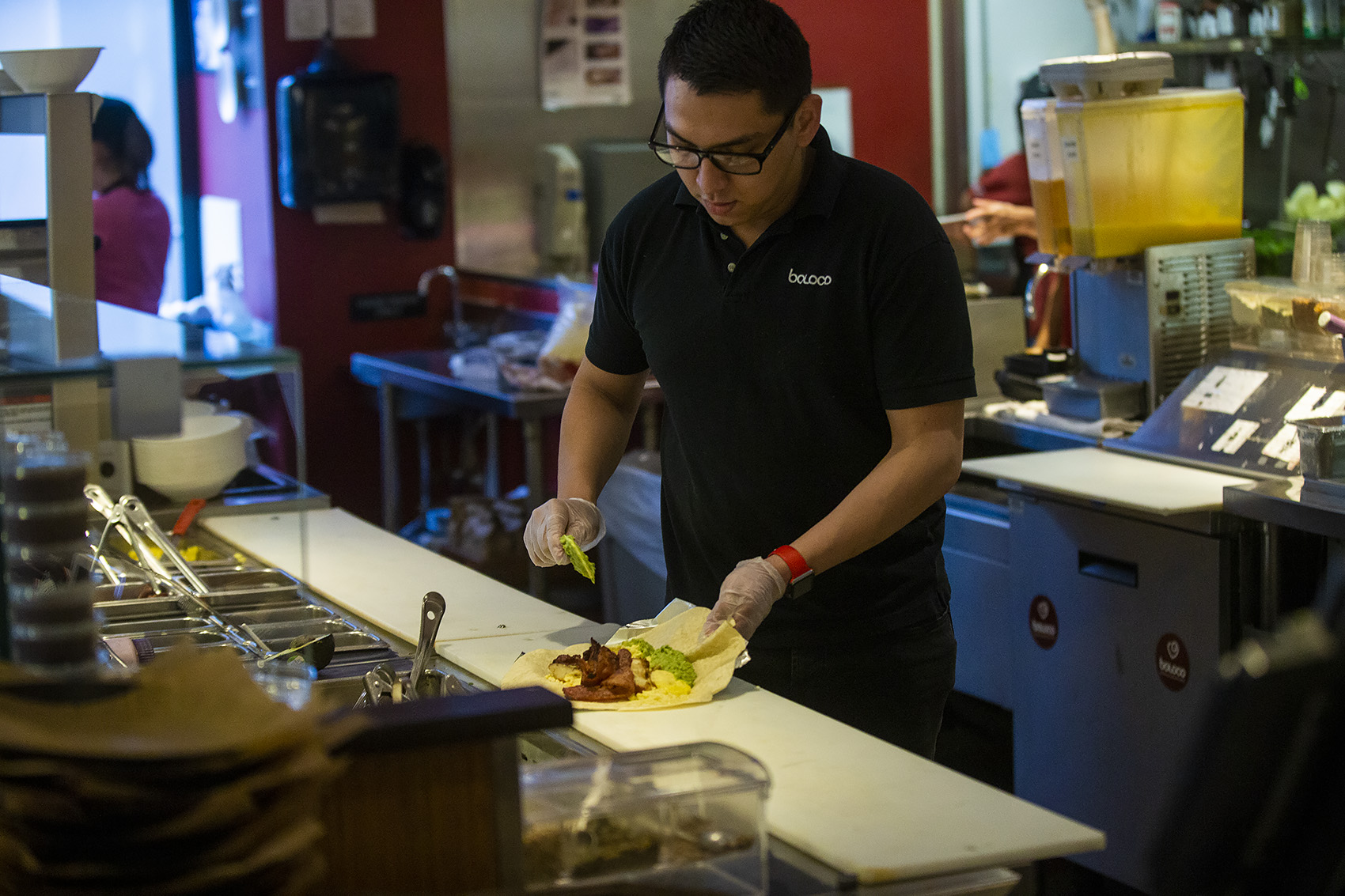 """Boloco manager Erick Guitierrez slaps some guacamole onto a breakfast burrito he is making for a customer using the """"Food For All"""" app. (Jesse Costa/WBUR)"""