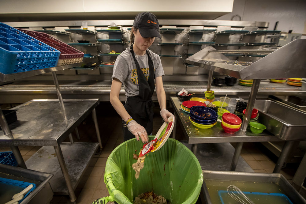 Sarah Anastasio cleans off a plate in Kimball Dining Hall at The College of the Holy Cross. (Jesse Costa/WBUR)