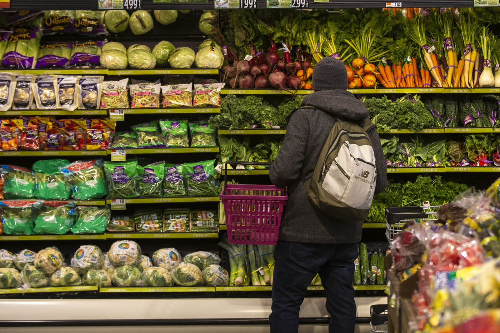 A customer peruses the produce at Roche Bros. in West Roxbury. (Jesse Costa/WBUR)