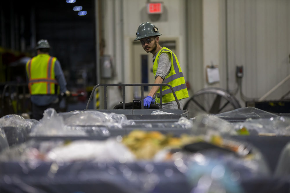 A worker moves a bin of discarded food from a Stop & Shop store before the food is processed and fed into the company's anaerobic digester. (Jesse Costa/WBUR)