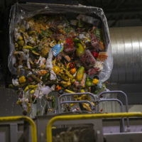 A bin of expired food from area Stop & Shop stores being poured into the anaerobic digester at the Stop & Shop Distribution Center in Freetown. (Jesse Costa/WBUR)
