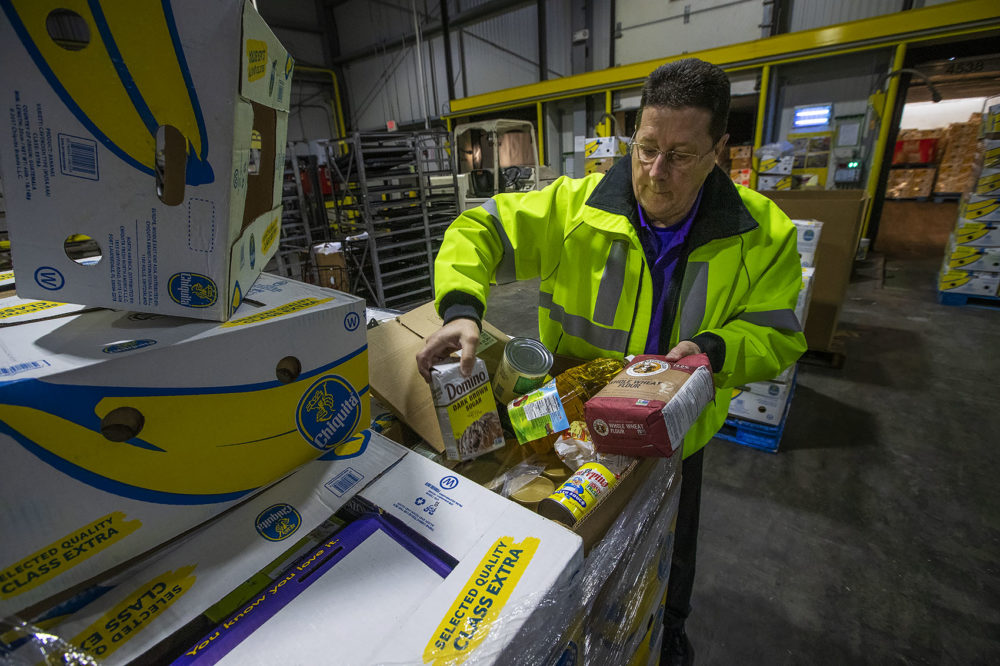 Roger Beliveau, Stop & Shop's manager of distribution services, shows some of the items being sent to the Greater Boston Food Bank. (Jesse Costa/WBUR)