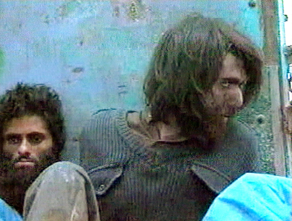 This image from television footage made in Mazar-i-Sharif, Afghanistan in 2001 shows John Walker Lindh at right, claiming to be an American Taliban volunteer calling himself Abdul Hamid. (AP Photo/APTN)