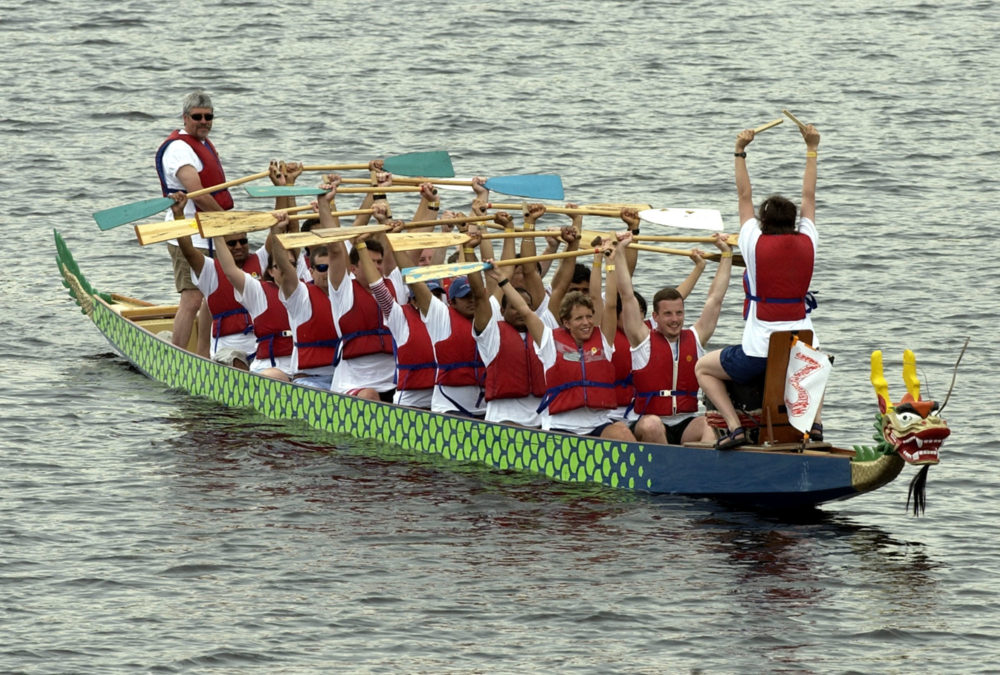The drummer, right, at the bow of the boat leads a crew in some pre-race stretching before the start of competition at the Dragon Boat Festival on the Charles River in Cambridge in 2002. (Robert E. Klein/AP)