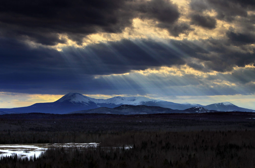 In this March 19, 2010 photo, sun rays filter through clouds over 5,267-foot Mount Katahdin in Maine's Baxter State Park. (Robert F. Bukaty/AP)