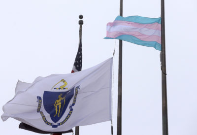 In this 2016 file photo, a flag representing the transgender community, foreground, flies next to the Massachusetts state flag and a U.S. flag in front of Boston City Hall. (Steven Senne/AP)