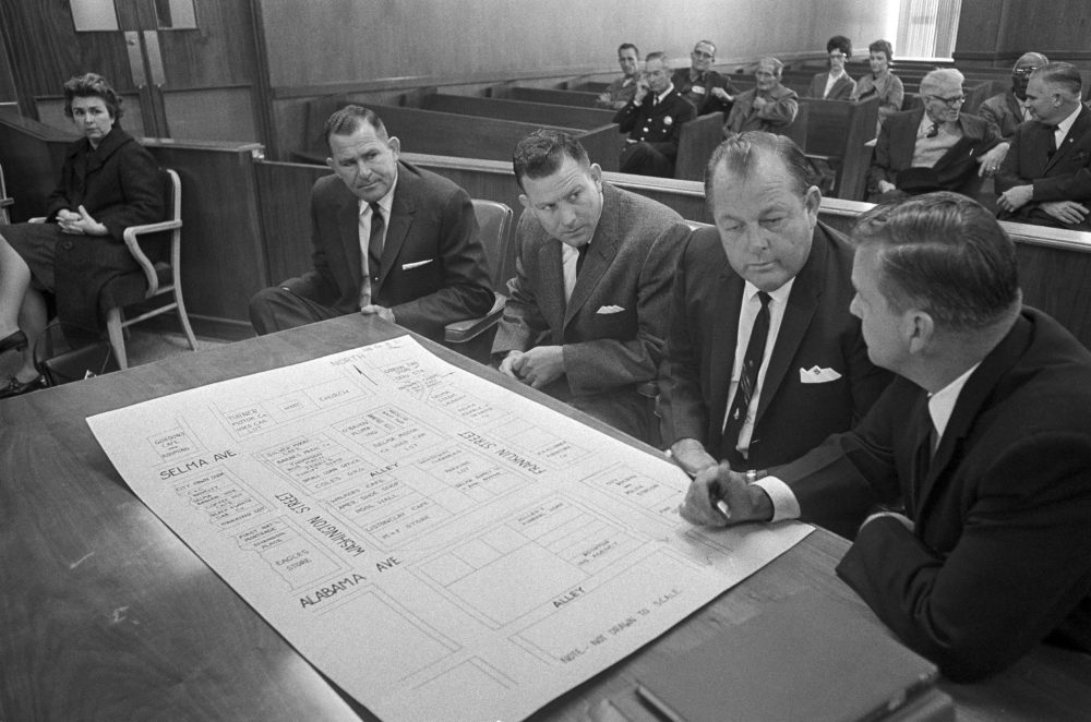 In this 1965 file photo, three defendants go over a street diagram of an area in Selma, Ala., where the clubbing death of a Unitarian Universalist minister, Rev. James Reeb, took place. (Horace Cort/AP)