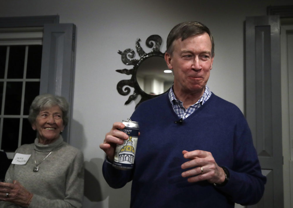 Former Colorado Gov. John Hickenlooper smiles after sipping a New Hampshire craft beer called The Gov'nah at a campaign house party on Feb. 13, 2019, in Manchester. (Elise Amendola/AP)