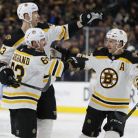 Boston Bruins left wing Brad Marchand (63) celebrates with teammates Zdeno Chara, back left, and Patrice Bergeron after scoring during a game this season. (John Locher/AP)