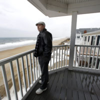 Real estate agent Tom Saab stands on a oceanfront deck at a condo he developed in Salisbury. Academic researchers say concerns over rising sea levels and increased flooding are having subtle but significant impacts on coastal property values. (Elise Amendola/AP)